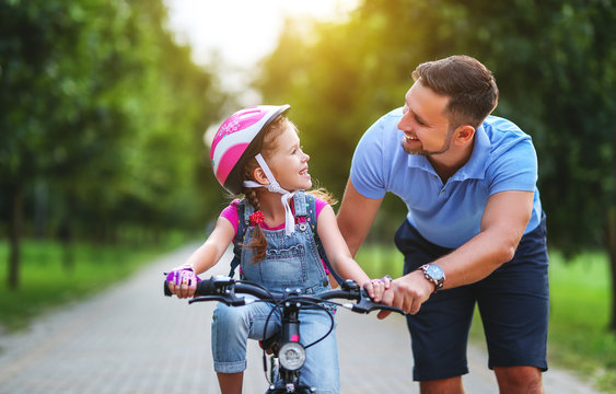 happy family father teaches child daughter to ride a bike in the Park  .