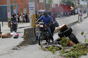 People ride a motorbike past a barricade set up with tires and tree branches, as people are protesting against a shortage of fuel, in a street of Port-au-Prince