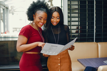 two beautiful and stylish young, dark girls standing in a restaurant and look in to menu