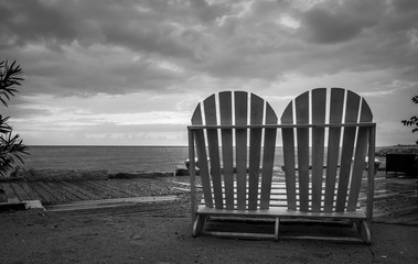 Black and white picture of doubled beach chairs