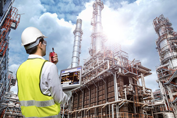 Double exposure of engineers holding walkie talkie are working orders the oil and gas refinery plant. Industry concept image.