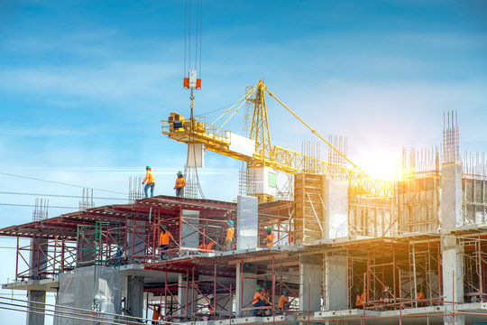 Workers are working on large construction sites and many cranes are working in the construction industry.