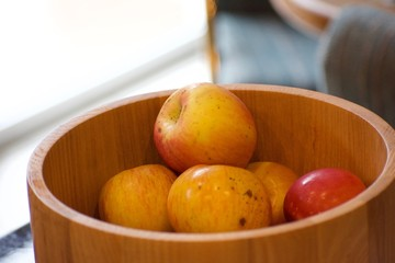 Red and yellow apples sitting in a wooden bowl