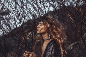 portrait of beautiful young woman through dry branches outdoors