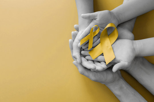 adult and children hands holding yellow gold ribbon, Sarcoma Awareness, Bone cancer, childhood cancer awareness, World Suicide Prevention Day, September Yellow