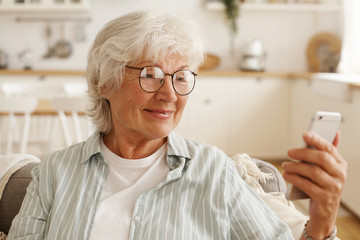 Happy joyful female pensioner in round eyeglasses surfing internet on cell phone, looking at mobile's screen with broad smile, booking plane tickets, planning trip or scrolling pics via social network