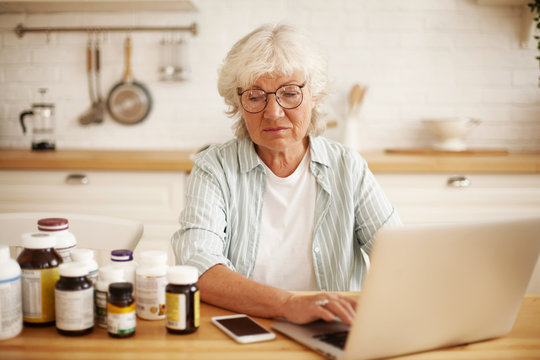Displeased elderly retired European woman in round eyewear sitting in kitchen, looking at bottles of food dietary supplement with despise, typing angry negative review on website using laptop