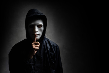 Male hacker hidden face with the mask in the dark. Technology, cyber crime concept.