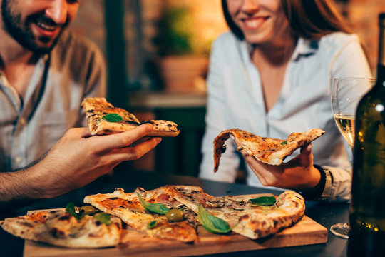 close up of people eating pizza