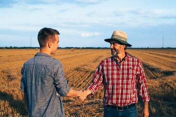 partnership handshake. two ranchers handshake on field