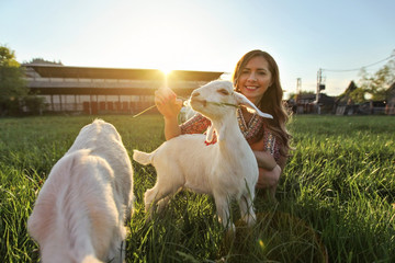 Young woman feeding grass to goat kids, wide angle photo with strong backlight and sun over farm in background