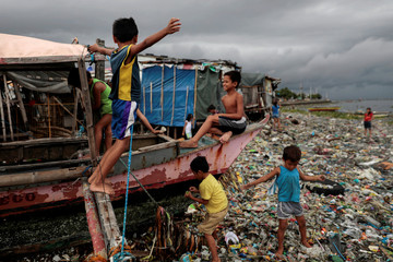 Children play on a boat docked on the garbage-filled shore of Baseco Beach in Tondo