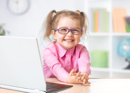 Happy kid in spectacles with notebook in room