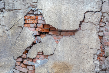 Cracked plaster on a brick wall
