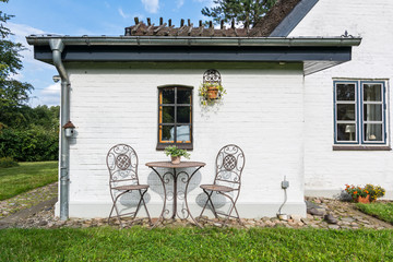 Peaceful garden with two chairs in front of whitewashed historic house in Northern Germany