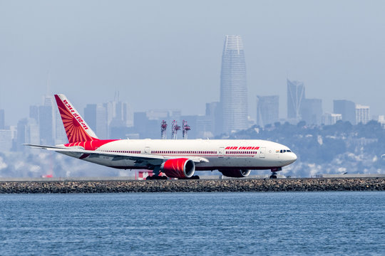 August 31, 2019 Burlingame / CA / USA - Air India aircraft preparing for take off at San Francisco International Airport (SFO); San Francisco skyline visible in the background