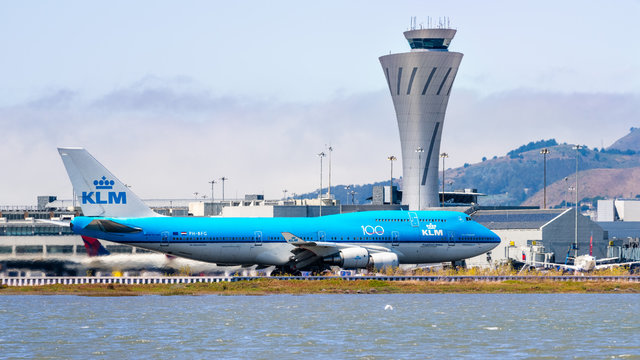 September 1, 2019 Burlingame / CA / USA - KLM aircraft preparing for take off at San Francisco International Airport (SFO); Traffic control tower visible in the background