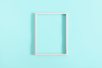 Empty pink photo frame on pastel blue  background. Flat lay, top view, copy space