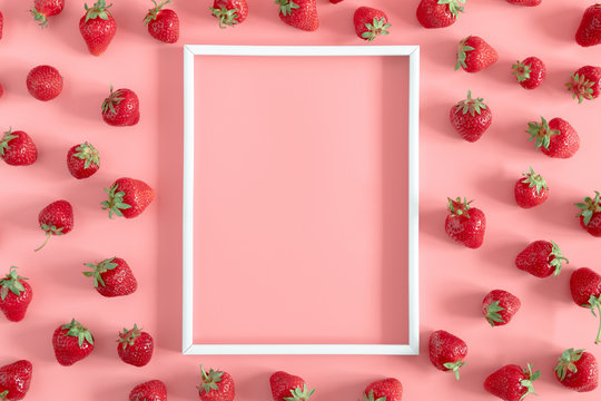 Strawberries on pink background. Blank frame for text, strawberries berries pattern. Creative food concept. Flat lay, top view, copy space