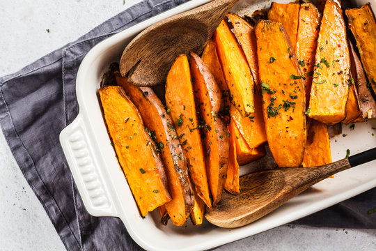 Baked sweet potato slices with spices in oven dish. Healthy vegan food concept.