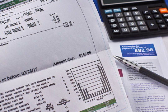 Comparison of utility bills in dollars and pounds. Utility bill sheets, calculator and pen. Close-up