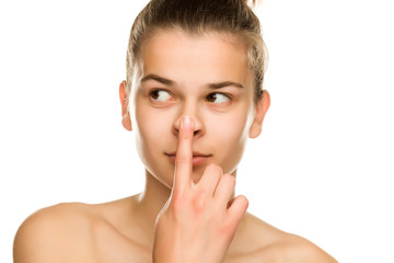 young beautiful woman touches her nose on white background