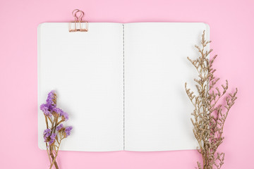 Top view of notebook stationery and flower on pink background