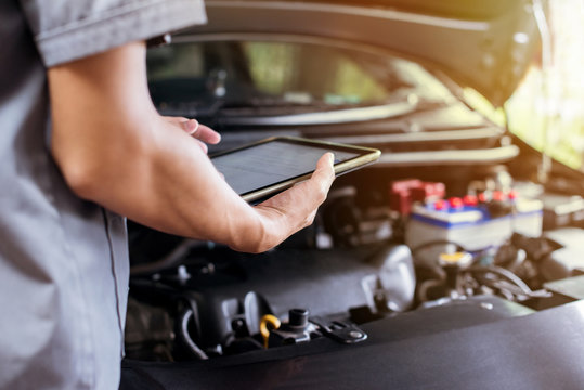 The mechanic uses a tablet to check the engine.