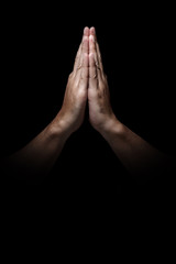 Man hands in praying position low key image. High Contrast isolated  on Black Background. Copy Space.