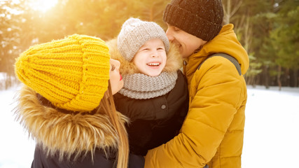 Portrait of happy family in winter day. Mom and dad are cuddling and kissing their little son in winter park. Family lovely moments.