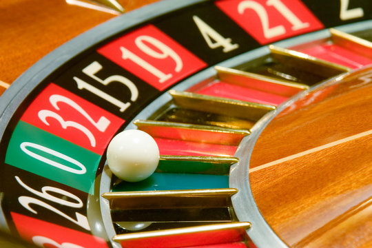 Roulette table in casino, with many games and slots, roulette wheel in the foreground.