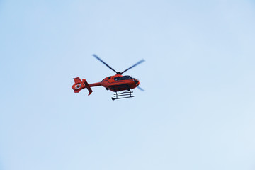 Fotobehang Helicopter Rescue Helicopter or Air ambulance - red air medical services heli copter midair against blue sky