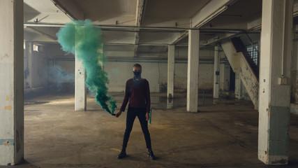 Man holding a smoke maker inside an empty warehouse