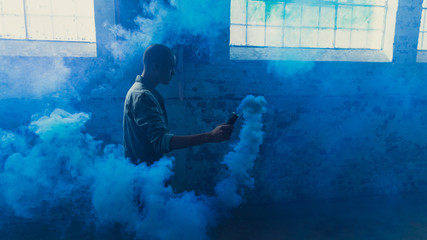 Man holding blue distress flare inside empty warehouse