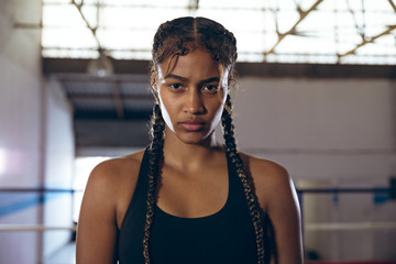 Female boxer looking at camera in boxing club
