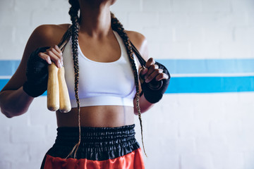 Midsection of boxer with skipping rope in boxing club
