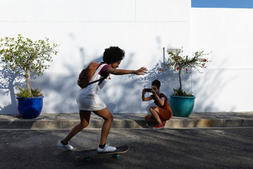Woman taking picture of her friend skateboarding on road