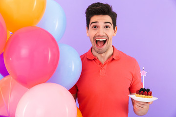 Image of optimistic joyful man celebrating birthday with multicolored air balloons and piece of pie