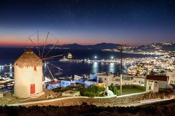 Wall Mural - Blick über die Stadt von Mykonos am Abend mit einer traditionellen Windmühle und Sternenhimmel, Kykladen, Griechenland