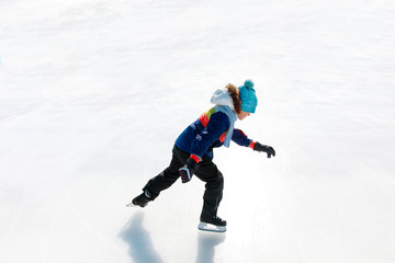 child skating on ice in winter nature