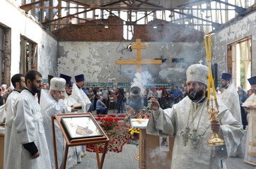 A priest leads a religious service marking the 15th anniversary of the deadly school siege in the town of Beslan