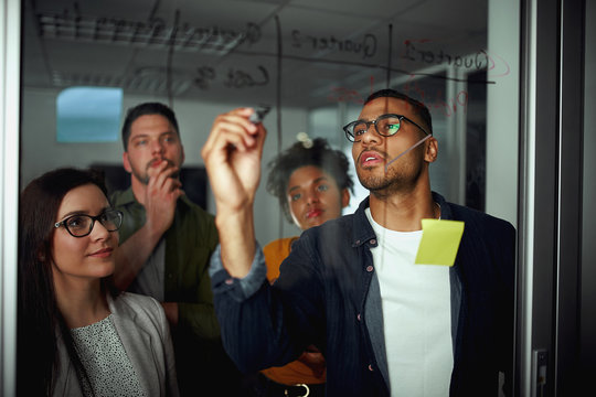 Pensive diverse group of young people looking at businessman writing business future plans on glass during office meeting