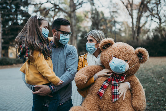 Young family in protective mask outdoors in park. Air pollution concept.