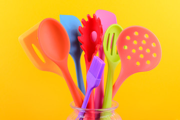 bright multi colored kitchen utensils on yellow background