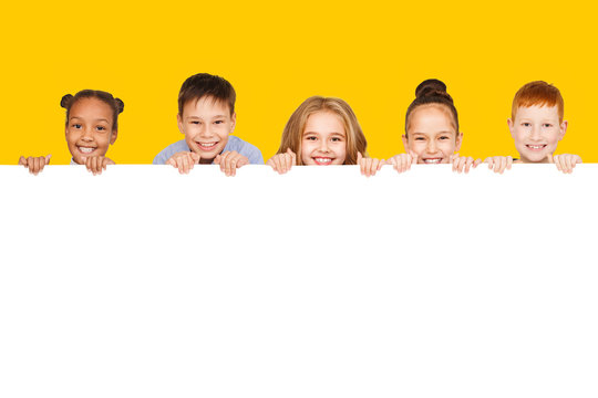 Happy children with empty board, yellow background