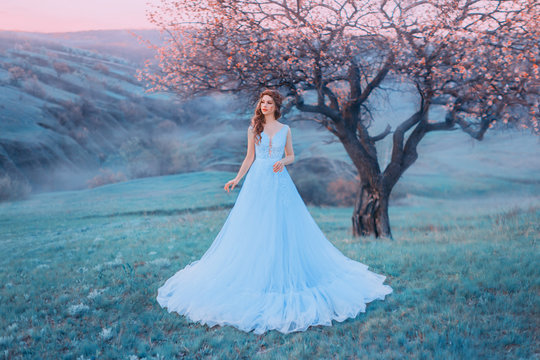 incredible woman stands in the background of a mountain landscape in a blue dress. Tale of Cinderella with a doll face. Cold color. Delicate pink sky and a blossoming tree on a hill. Art photography