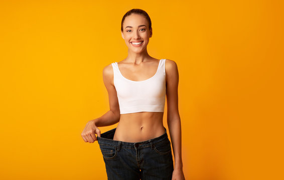 Slim Girl In Oversize Jeans Standing In Studio, Yellow Background