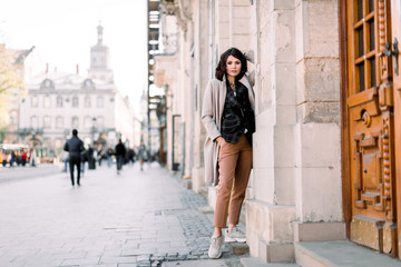 Outdoor portrait of high fashion female model in stylish clothes, coat and pants, posing in the old city street Wall mural