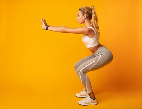 Young Lady Doing Deep Squat Exercise, Studio Shot, Side View