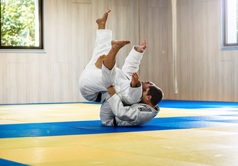Two adult man practicing judo in the sports hall.